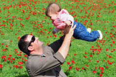 Father and Daughter in Flowering Field. An image of a baby girl and father sitting and having fun in a green field with red poppies Royalty Free Stock Images
