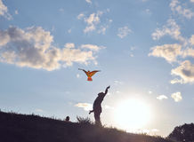 Father with daughter is flying toy kite. A man with his daughter is flying toy kite at sunset time. On windless day this toy should be thrown up in the air so Stock Image
