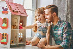 Father and daughter girl play. Happy father and daughter girl play with doll house at home. Funny lovely family is having fun in kids room royalty free stock photo