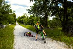 Father and daughter going in bicycle. Little girl falling off her bicycle Royalty Free Stock Images
