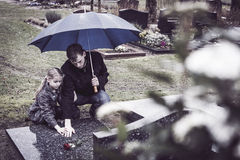 Father and daughter at grave. Widower and daughter kneeling at deceased mothers grave at graveyard. Mourning her death royalty free stock images