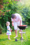 Father and daughter grilling in the garden