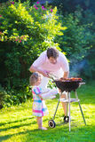 Father and daughter grilling meat Stock Images