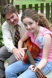 Father Daughter Guitar Lesson 3. A father teaching his daughter to play guitar stock images