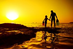 Father and daughter hand in hand on the rock, Croatian cost, seaboard. Father and daughter swimmers hand in hand on the rock with sunset in background. Croatian Royalty Free Stock Photos