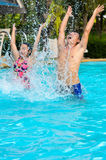 Father and daughter have fun in the pool. Father and daughter are having fun splashing in the pool Stock Image