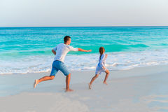 Father with daughter have fun on white tropical beach on caribbean island in sunset light Stock Image