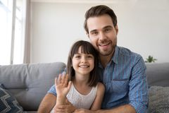 Father and daughter have video call sitting on couch. Head shot portrait of cheerful diverse family young men sitting on sofa at home with daughter have video stock image