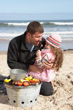 Father And Daughter Having Barbeque On Beach royalty free stock photos