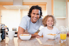 Father and daughter having cereals in the kitchen together Royalty Free Stock Images