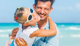 Father and daughter having fun on beach Stock Images