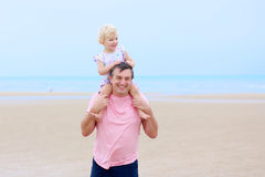 Father with daughter having fun on the beach Stock Photos