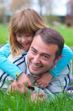 Father and daughter having fun in the grass royalty free stock image