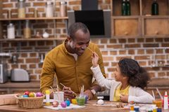 Father and daughter having fun and painting faces, easter concept. African american father and daughter having fun and painting faces, easter concept Stock Photos
