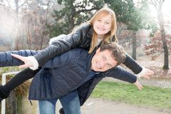 Father and daughter having a fun piggyback in autumn winter park Family royalty free stock images