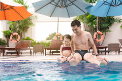 Father and daughter having fun in the pool. Summer holidays and Royalty Free Stock Image