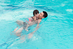 Father and daughter having fun in the pool. Summer holidays and Royalty Free Stock Images