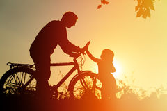 Father and daughter having fun riding bike at sunset, active family sport Royalty Free Stock Images