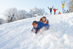 Father And Daughter Having Fun Sledging Down Hill Royalty Free Stock Photos