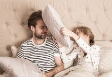 Father and daughter having pillow fight in a bed Royalty Free Stock Photos