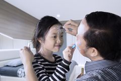 Father and daughter having quality time playing with face painting Stock Photo