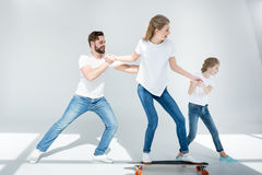 Father and daughter helping young woman riding skateboard Royalty Free Stock Photos