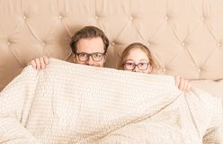 Father and daughter hiding under a duvet in a bed stock photos