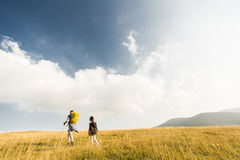 Father and daughter hiking. Young father and daughter enjoy hiking on a sunny day royalty free stock image