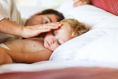 Father and daughter. Father and his adorable toddler daughter relaxing in bedroom royalty free stock images