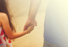 Father and daughter holding hand in hand. In summer day Stock Photo