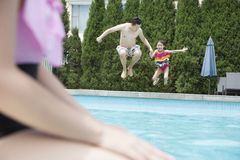 Father and daughter holding hands and jumping into the pool Stock Images