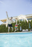 Father and daughter holding hands and jumping into the pool Royalty Free Stock Photos