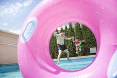 Father and daughter holding hands and jumping into the pool, seen through an inflatable pink tube Stock Images