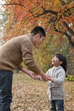 Father and daughter holding hands, looking at each other in the park, autumn Royalty Free Stock Photo