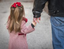 Father and daughter holding hands. Rear view of a father and young daughter having tender moment holding hands Stock Images
