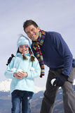 Father and daughter (7-9) holding snow balls, standing together in snow field, smiling, portrait Royalty Free Stock Photography