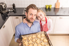 Father and daughter holding tray with homemade cookies Stock Photography