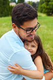 Father And Daughter Hugging In Park. Family Embracing Outdoors. Father And Daughter Hugging In Park. Happy Smiling Young Parent Embraces His Kid Outdoors. Dad royalty free stock image