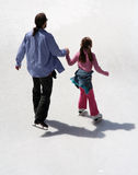 Father and daughter ice skating. Father and daughter are skating together holding hands Royalty Free Stock Photography