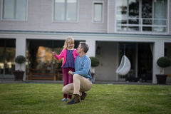 Father and daughter interacting with each other in garden. Smiling father and daughter interacting with each other in garden Stock Images