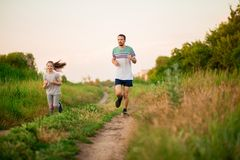 Father and daughter jogging. Cheerful father and daughter run in park together. stock photo