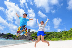 Father and daughter jumping on beach at Thailand Stock Photo