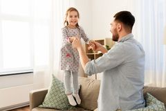 Father and daughter jumping and having fun at home stock photos