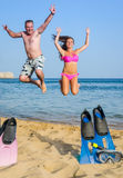 Father and daughter jumping on tropical beach Stock Images