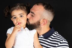 Father and daughter kiss hug in black background royalty free stock image