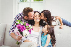 Father and daughter kissing mother sitting on sofa Royalty Free Stock Photos