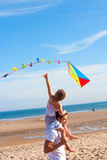 Father and Daughter with Kite on Beach Stock Images