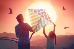 Father and daughter with kite. Happy family on summer walk! Father and daughter walking and having kite in mountains royalty free stock photos