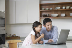 Father And Daughter With Laptop In Kitchen Royalty Free Stock Photography