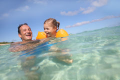 Father and daughter laughing together in the sea Royalty Free Stock Images